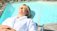 Closeup of woman relaxing in long chair by pool Stock Footage