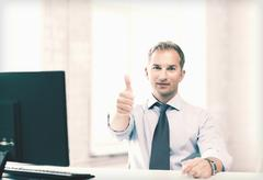 Smiling businessman showing thumbs up Stock Photos