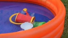Orange inflatable paddling pool with water - stock footage
