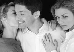 Man standing between two women, being kissed by one, b&w Stock Photos