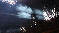 Smoke rising through gaps in grass roof Stock Footage
