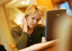 Mature woman using laptop, looking agitated - stock photo