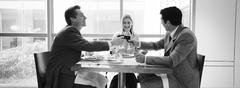 Two businessmen and woman sitting at table clinking glasses, b&w, panoramic view Stock Photos