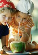 Two children drinking fresh juice through straws, close-up - stock photo
