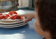 Young child with finger on cake, focus on hand. - stock photo