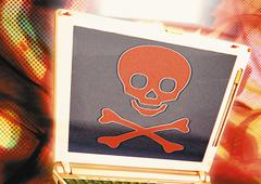 Laptop with skull and crossbones, digital composite. - stock photo
