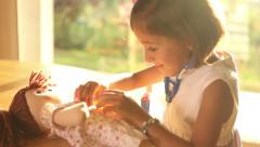 Girl playing doctors with doll Stock Footage