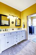 Beautiful  vanity cabinet in bright yellow bathroom Stock Photos