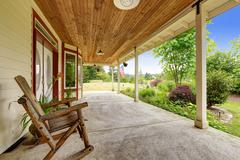 farm house exterior. entrance porch with rocking chair - stock photo