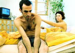 Stock Photo of Couple in bed, man sitting semi-naked, woman pointing.