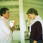 Stock Photo of Mature couple standing face to face, arguing, woman holding head