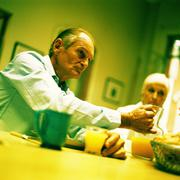 Mature couple sitting at table, man holding pitcher Stock Photos