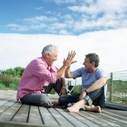 Mature men sitting together, slapping hands in air, on deck outside Stock Photos