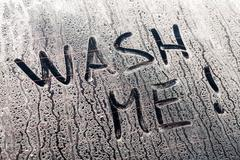 Wash me words on a dirty car window Stock Photos