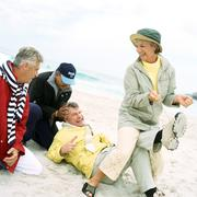 Mature group playing on beach, woman pulling man's laces Stock Photos