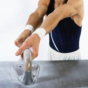 Male gymnast gripping handle on pommel horse, mid section Stock Photos
