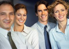 Four people smiling into camera, head and shoulders - stock photo