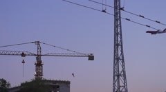 Civil airplane lands over construction cranes-slow motion Stock Footage
