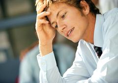 Young man in business attire holding head and looking down, head and shoulders, Stock Photos