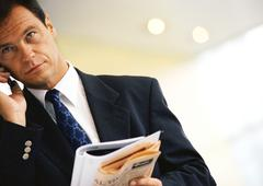 Businessman using cell phone, holding newspaper, portrait. Stock Photos