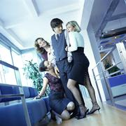 Three young women office workers surrounding male colleague. Stock Photos