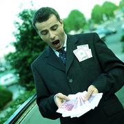 Stock Photo of Businessman holding bills fanned out, portrait.