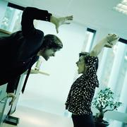 Woman threatening to throw object at man with arm raised in office. Kuvituskuvat
