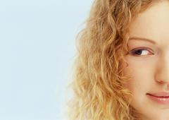Young woman looking out of corner of eye, one side of face, close-up, portrait. Stock Photos