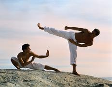 Two men performing martial arts, one defending, one attacking Stock Photos