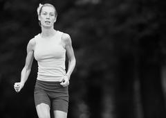 Woman in sports clothes running, three quarter length, b&w - stock photo