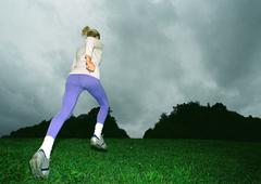 Woman running on grass, rear view, full length, low angle view, silhouette of Stock Photos