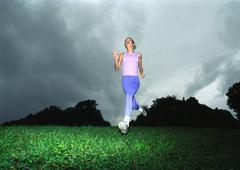 Woman running, low angle view Kuvituskuvat