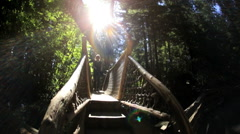Female walker Capilano suspended Treetop forest walkway Canada Stock Footage