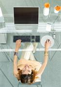 Woman at table with screen and keyboard, high angle vew Stock Photos