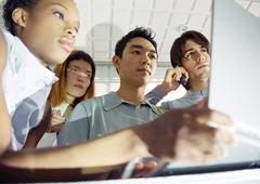 Four young people, one holding laptop, low angle view Stock Photos
