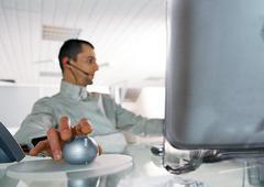 Man at desk using cordless mouse - stock photo