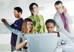 Group of people gathered around computer Kuvituskuvat