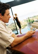 Man using cell phone, woman standing by terrace in background Stock Photos