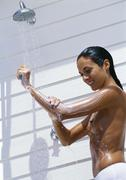 Semi-nude woman taking shower outdoors Stock Photos