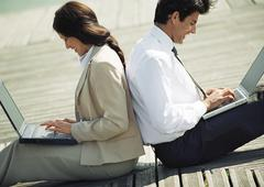 Businessman and woman back to back on ground with laptop computers on laps Stock Photos