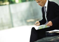 Businessman sitting outdoors, examining documents Stock Photos