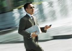 Businessman walking with cell phone in hand, three quarter length, tilt - stock photo