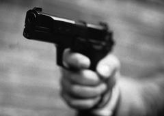 Hand holding gun, close-up, b&w - stock photo