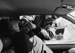 Man holding gun to woman's neck through car window, b&w Stock Photos