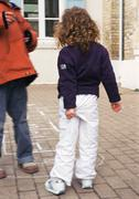 Two children, one pulling at pants, rear view Stock Photos