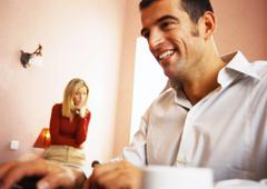 Man smiling, woman watching in background. Stock Photos