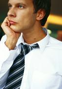 Businessman with hand under chin, portrait - stock photo