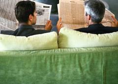Businessmen sitting side by side with newspapers, rear view Stock Photos