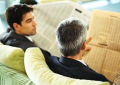 Businessmen sitting reading newspapers, rear view, head and shoulders Stock Photos