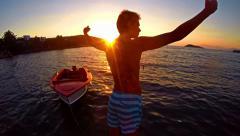 Freedom concept, crane shoot of successful man raising hands toward ocean sun Stock Footage